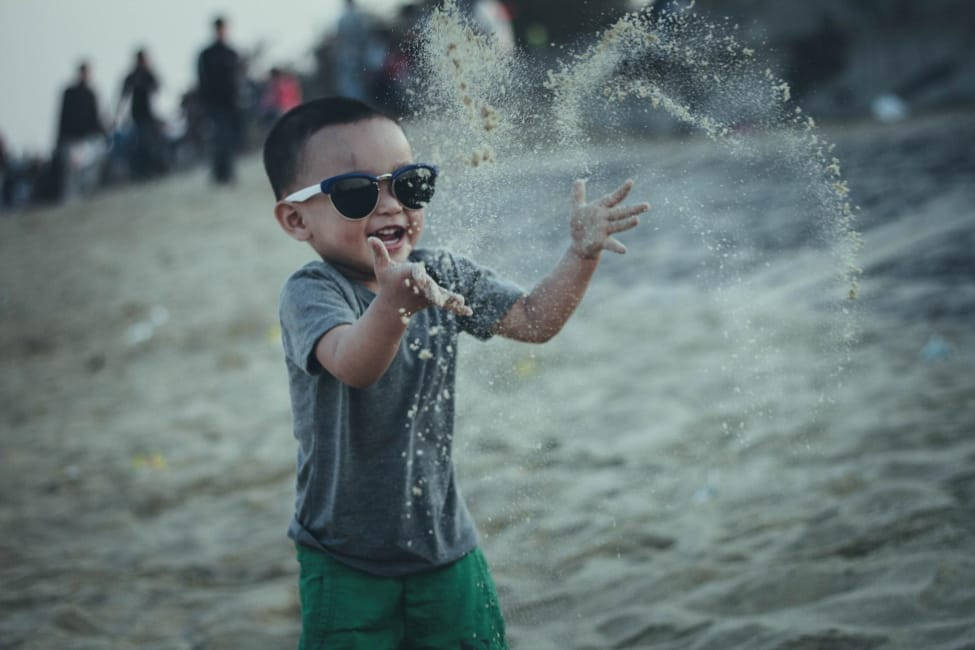 Boy wearing sunglasses playing in the sand